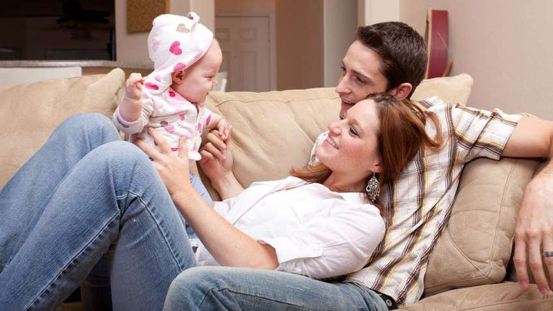 A young couple cuddles on a couch at home while they hold their baby daughter.