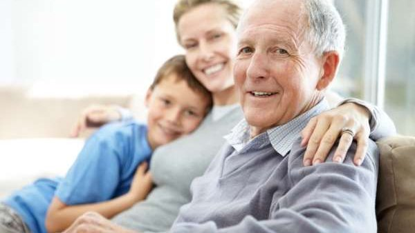 An older man sits on a couch with his grown daughter and grandson.