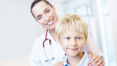 A female doctor with a young male patient.