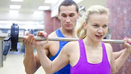 A personal trainer helps a female client lift weights.