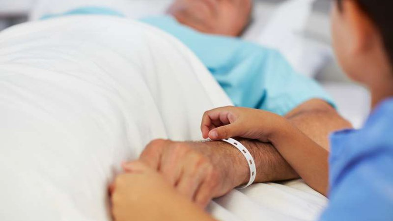 A patient lies in a hospital bed while a family member holds his hand.