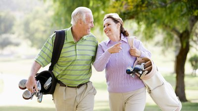 An older couple walks on the golf course, carrying their golf equipment.