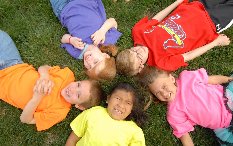 A group of kids lay in the grass.