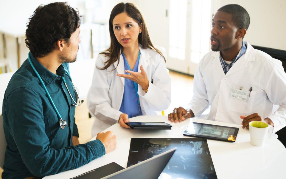A group of CoxHealth medical professionals examine a chart.
