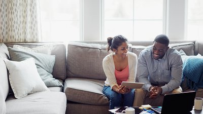 A young couple sits on their couch, reviewing health insurance options