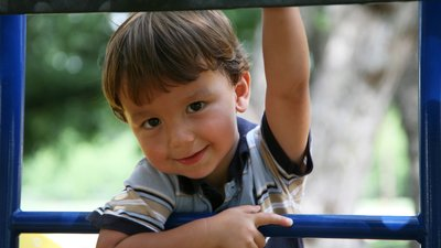 A child plays on outdoor playground equipment at a Cox Learning Center.