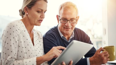 A couple reviews patient rights and client responsibilities information on a tablet computer.