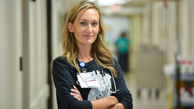 A CoxHealth nurse stands in a hallway.