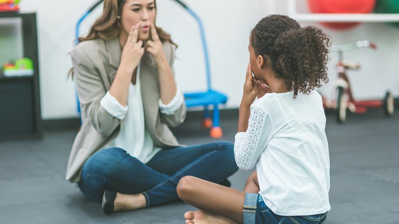 A speech therapist works with a child.