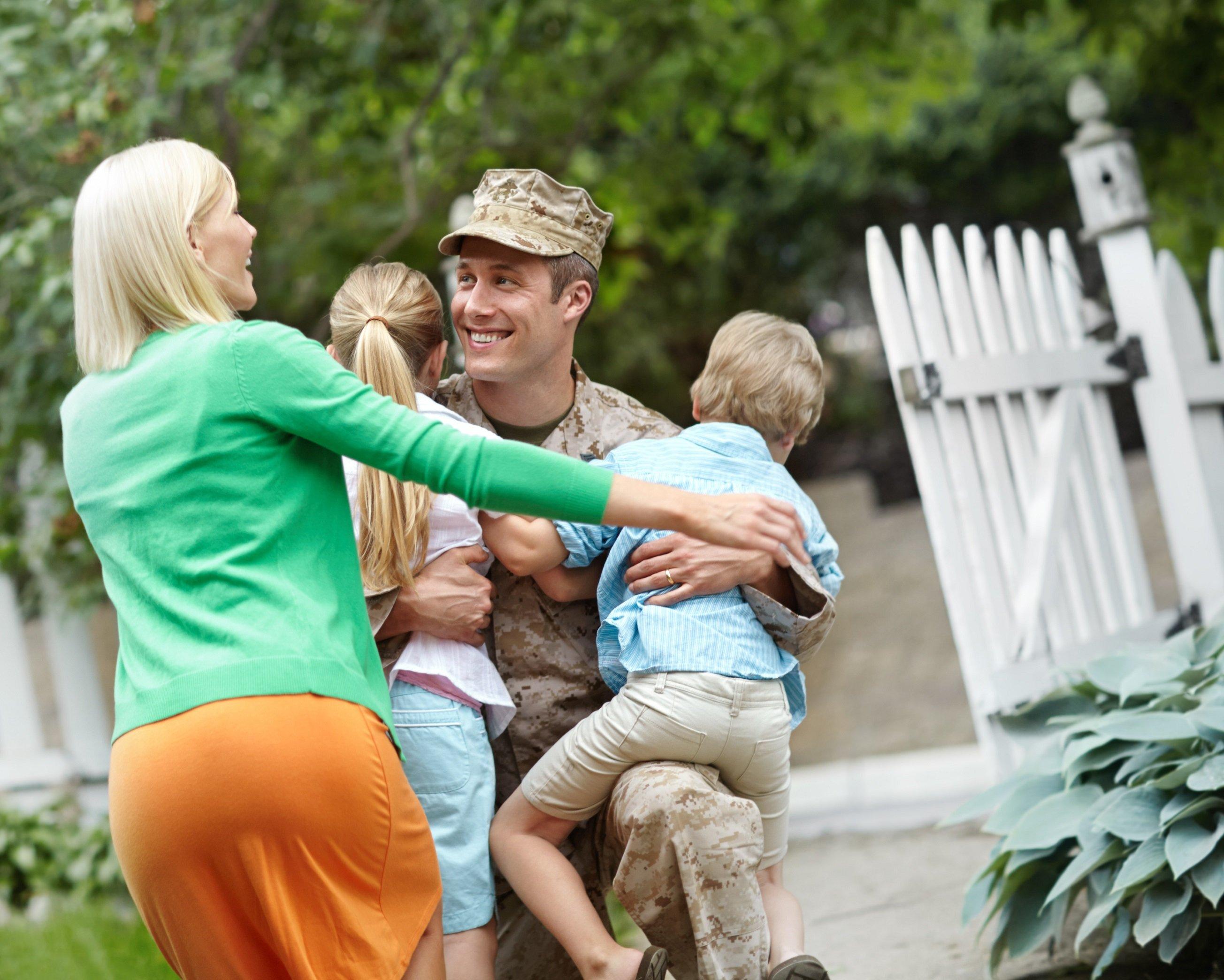 A veteran hugs his family.