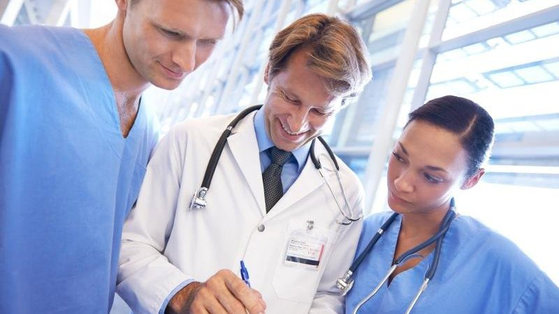 Two students learn from a doctor in their clinical rotations.
